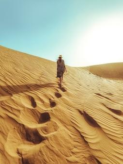 Młoda piękna kobieta w długiej sukni idzie wzdłuż wydm pustyni dubaju