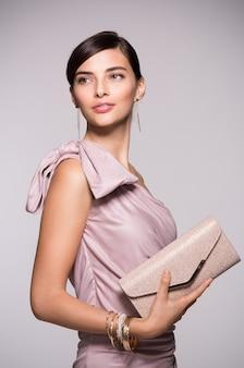 Młoda piękna kobieta w eleganckiej różowej sukience trzymając sprzęgło i odwracając