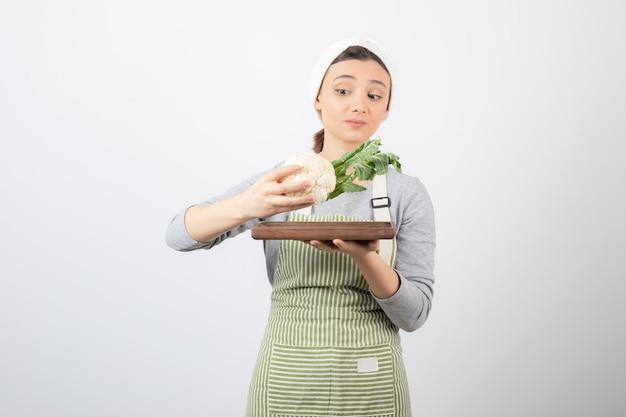 Młoda piękna kobieta w fartuchu patrząca na talerz kalafiora