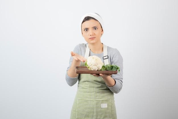 Młoda piękna kobieta w fartuchu pokazująca talerz kalafiora