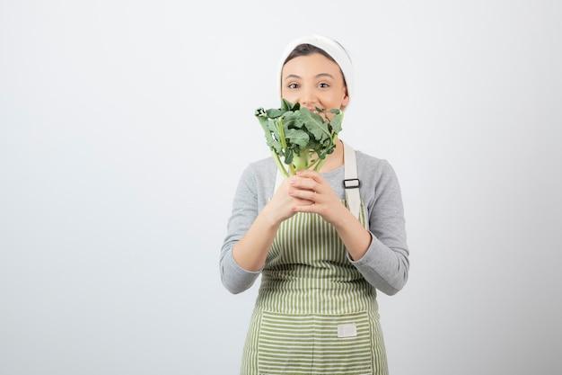 Młoda piękna kobieta w fartuchu pozuje ze świeżymi brokułami na białym tle