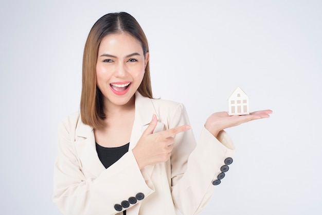 Młoda piękna kobieta w garniturze trzyma mały modelowy dom na białym tle studio