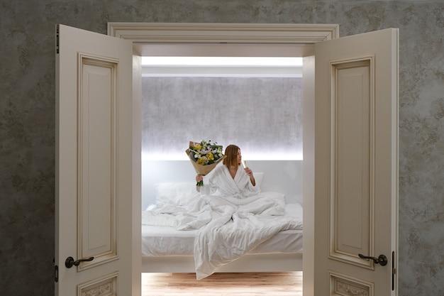 Młoda piękna kobieta w hotelu pije szampana w łóżku. świętowanie urodzin w sypialni