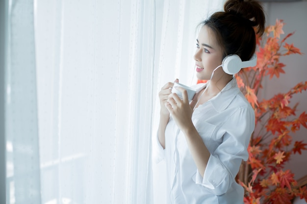 Młoda piękna kobieta w jasnym stroju, ciesząc się muzyką w domu