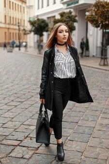 Młoda piękna kobieta w jesienny płaszcz z stylowe buty w paski bluzka na ulicy
