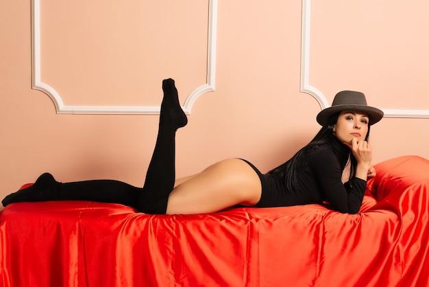 Młoda piękna kobieta w kapeluszu i czarnym ciele, leżąc na czerwonej kanapie. - wizerunek