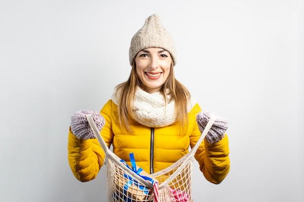 Młoda piękna kobieta w kapeluszu świętego mikołaja z torby na zakupy na białym tle