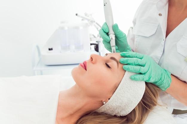 Młoda piękna kobieta w klinice kosmetologów mezoterapia frakcyjna na twarz