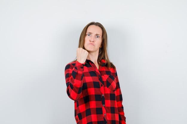 Młoda piękna kobieta w koszuli dorywczo ostrzeżenie z pięścią i patrząc wściekły, widok z przodu.