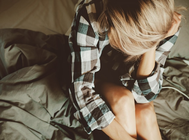Młoda piękna kobieta w koszuli na co dzień na łóżku