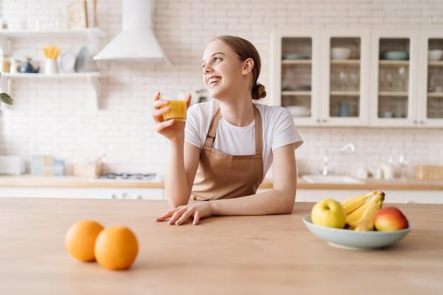 Młoda piękna kobieta w kuchni w fartuchu, owocach i soku pomarańczowym