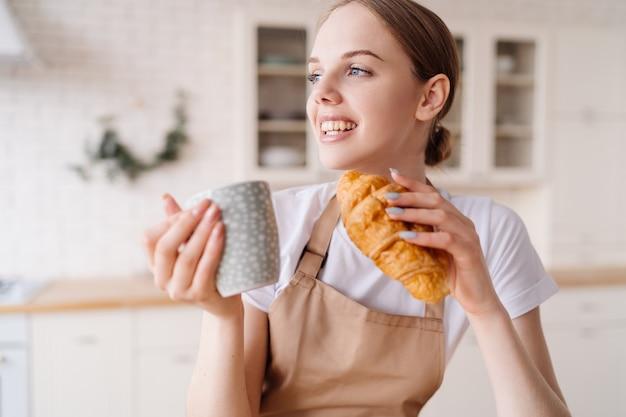 Młoda piękna kobieta w kuchni w fartuchu z kawą i rogalikiem cieszy się swoim porankiem
