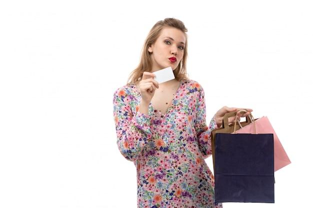 Młoda piękna kobieta w kwiatowej koszuli i czarnych spodniach z przodu, trzymająca paczki z zakupami przedstawiające białą kartę