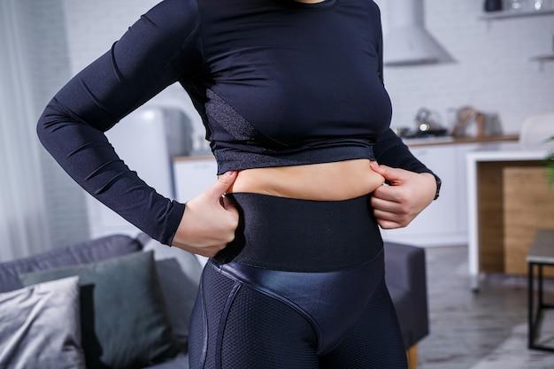 Młoda piękna kobieta w legginsach i topie pokazuje fałdę na brzuchu. zdrowy tryb życia. kobieta uprawia sport w domu. walka z nadwagą w domu