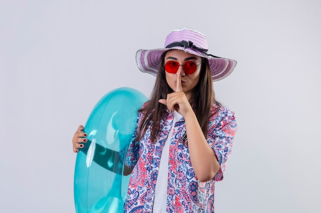 Młoda piękna kobieta w letnim kapeluszu i czerwonych okularach przeciwsłonecznych trzyma nadmuchiwany pierścionek wykonujący gest ciszy z palcem na ustach, gotowa do wakacyjnej koncepcji na białej ścianie