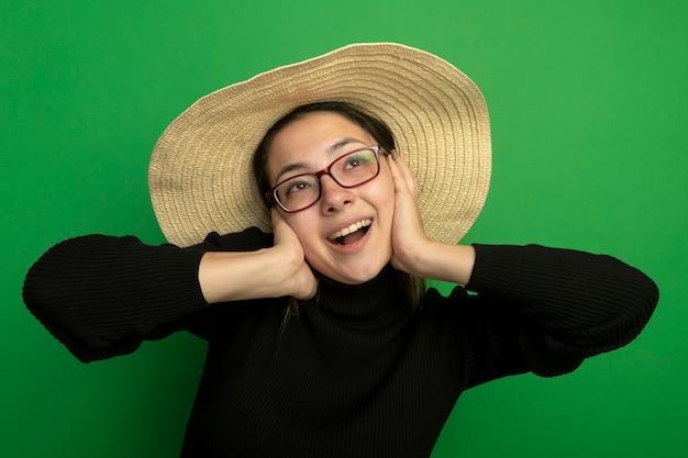 Młoda piękna kobieta w letnim kapeluszu w czarnym golfie i okularach patrząc w górę szczęśliwa i pozytywnie uśmiechnięta, wesoło stojąca nad zieloną ścianą