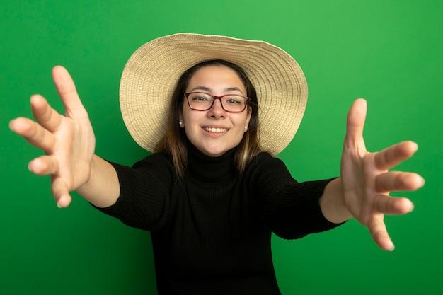Młoda piękna kobieta w letnim kapeluszu w czarnym golfie i okularach robi powitalny gest szczęśliwy i pozytywny uśmiechnięty przyjazny stojąc nad zieloną ścianą