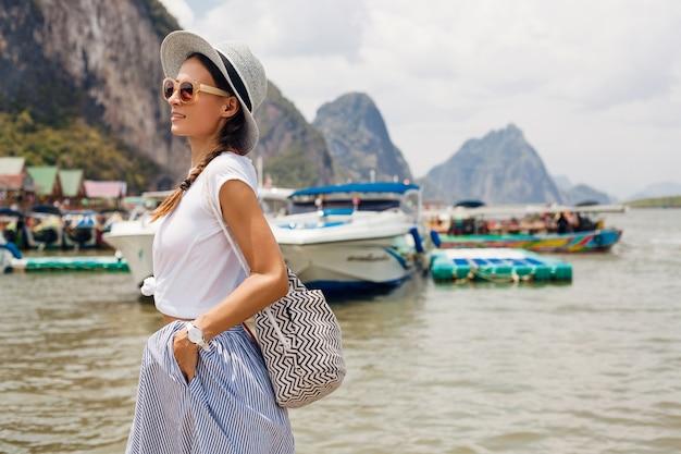 Młoda piękna kobieta w letnim stroju modowym, swobodnym stylu, podróżująca z plecakiem, kapeluszem, okularami przeciwsłonecznymi, wakacje w tajlandii, azji