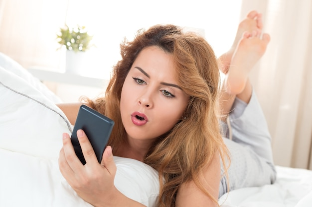 Młoda piękna kobieta w łóżku i patrząc na telefon komórkowy. poranny czas. szokujące wiadomości lub spóźniona koncepcja.