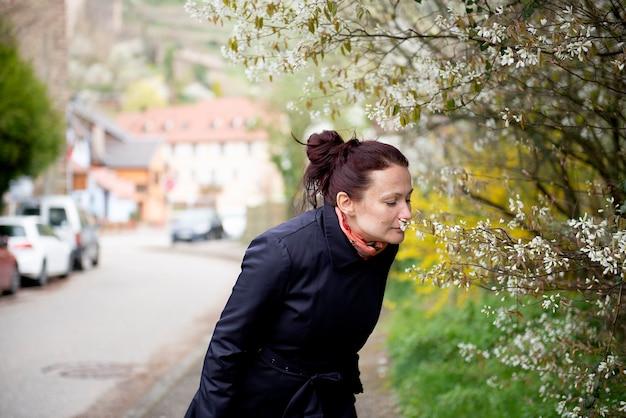 Młoda piękna kobieta w mieście na poboczu ulicy rozkoszuje się zapachem kwitnących wiosną drzew
