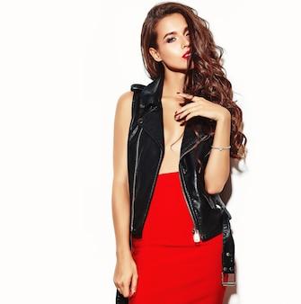 Młoda piękna kobieta w modnej letniej czerwonej spódnicy i czarnej skórzanej kurtce.