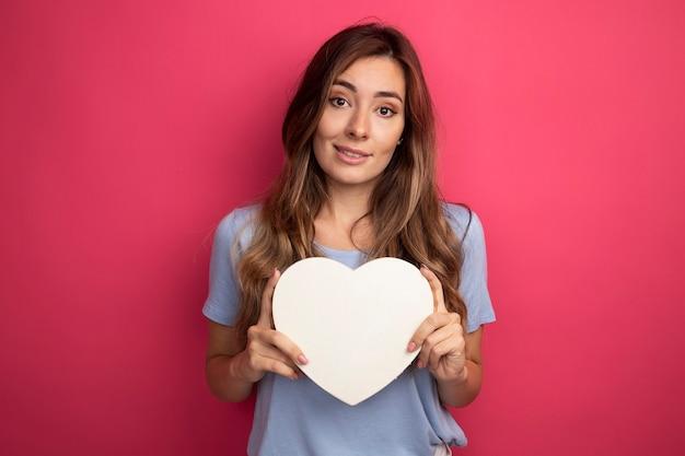 Młoda piękna kobieta w niebieskiej koszulce trzyma kartonowe serce patrząc na kamerę uśmiechając się radośnie stojąc na różowym tle