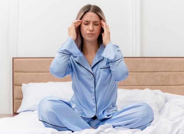Młoda piękna kobieta w niebieskiej piżamie siedzi na łóżku, dotykając jej tamples, mając silny ból głowy we wnętrzu sypialni na jasnym tle