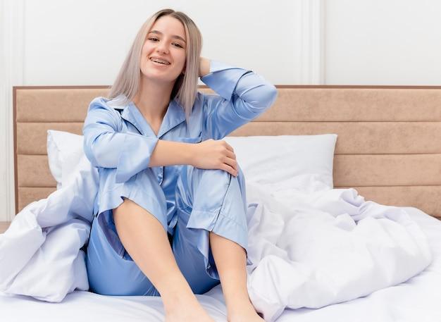 Młoda piękna kobieta w niebieskiej piżamie siedzi na łóżku szczęśliwa i pozytywnie uśmiechnięta i odpoczywa we wnętrzu sypialni