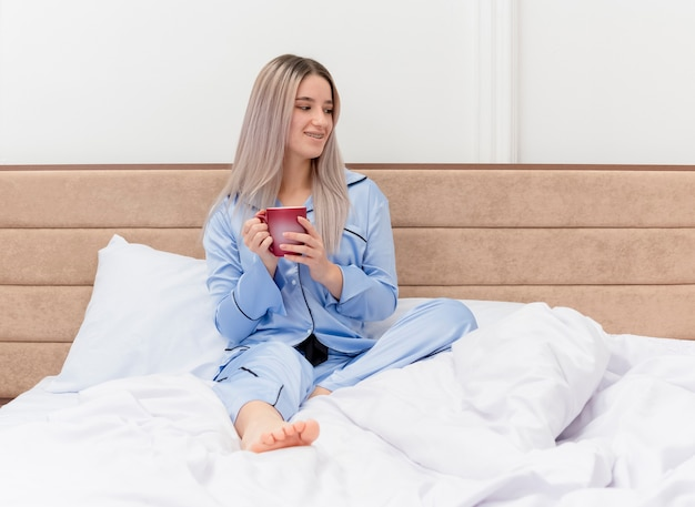 Młoda piękna kobieta w niebieskiej piżamie siedzi na łóżku z filiżanką kawy, patrząc na bok uśmiechając się, odpoczynek ciesząc się poranny czas we wnętrzu sypialni