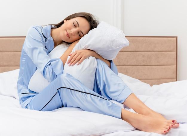 Młoda piękna kobieta w niebieskiej piżamie siedzi na łóżku z poduszką, czując pozytywne emocje, uśmiechając się z zamkniętymi oczami we wnętrzu sypialni