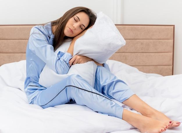 Młoda piękna kobieta w niebieskiej piżamie siedzi na łóżku z poduszką czuje pozytywne emocje z zamkniętymi oczami we wnętrzu sypialni na jasnym tle