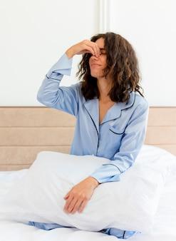 Młoda piękna kobieta w niebieskiej piżamie siedzi na łóżku z poduszką dotykając nosa między zamkniętymi oczami, czując poranne zmęczenie we wnętrzu sypialni na jasnym tle