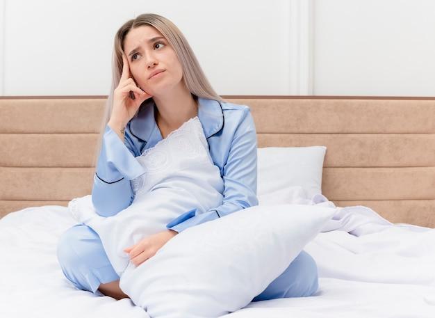 Młoda piękna kobieta w niebieskiej piżamie siedzi na łóżku z poduszką patrząc w górę zdziwiona we wnętrzu sypialni