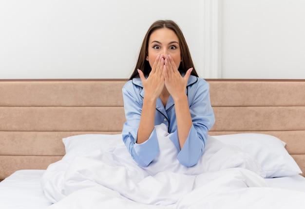 Młoda piękna kobieta w niebieskiej piżamie siedzi w łóżku, zdumiona i zaskoczona we wnętrzu sypialni