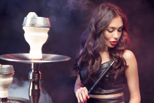 Młoda, piękna kobieta w nocnym klubie lub barze pali fajkę wodną lub sziszę