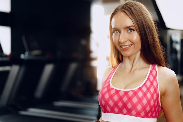 Młoda piękna kobieta w odzieży sportowej na siłowni