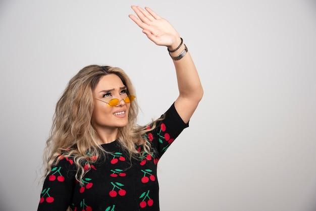 Młoda piękna kobieta w okularach pokazując rękę.