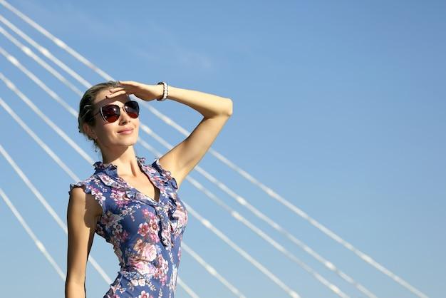 Młoda piękna kobieta w okularach przeciwsłonecznych, patrząc na słońce na niebieskim niebie
