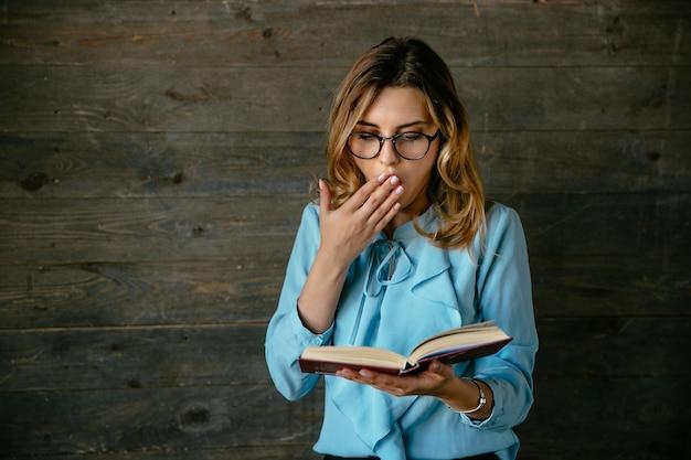 Młoda piękna kobieta w okularach wygląda na zszokowany, obejmuje jej otwarte usta