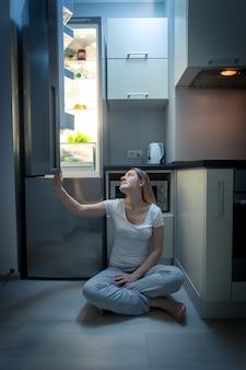 Młoda piękna kobieta w piżamie siedzi na podłodze w kuchni i patrzy na otwartą lodówkę późnym wieczorem