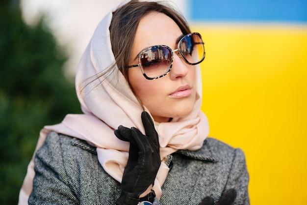 Młoda piękna kobieta w płaszczu siedzi na ławce w parku