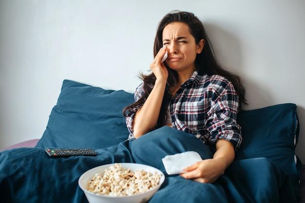 Młoda piękna kobieta w ranku łóżku w domu. płacz podczas oglądania filmu lub serialu melodramatycznego. trzymaj białą chusteczkę w dłoni i płacz.