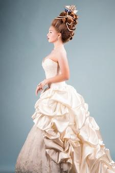 Młoda piękna kobieta w rocznika wiktoriański sukni z skomplikowaną fryzurą