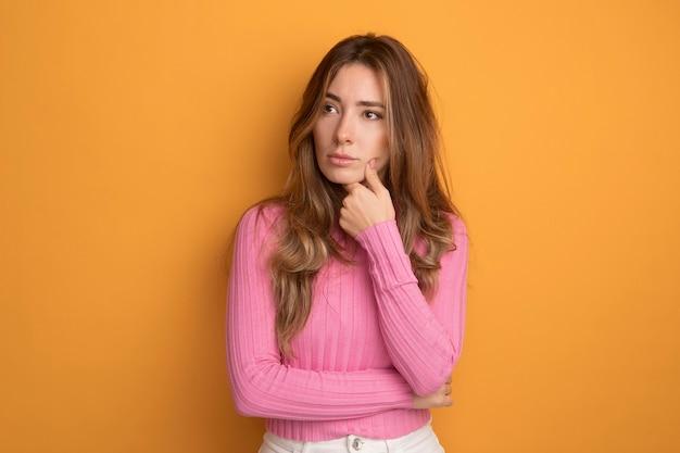 Młoda piękna kobieta w różowej bluzce, patrząca na bok z zamyślonym wyrazem twarzy, myśląca stojąc nad pomarańczą