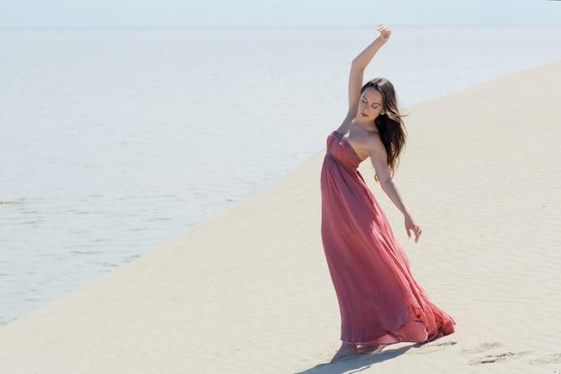 Młoda piękna kobieta w różowej sukience spaceruje po wydmach