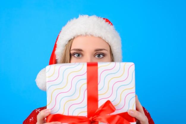 Młoda piękna kobieta w santa hat ukrywa twarz za dużym pudełkiem z czerwoną wstążką. na białym tle na szarym tle