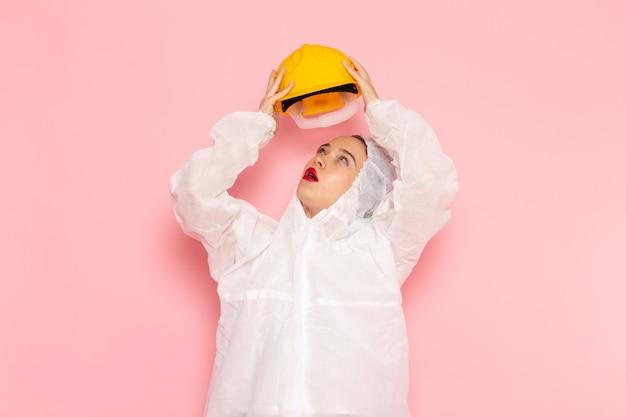 Młoda piękna kobieta w specjalnym białym garniturze i zdejmując żółty kask na różowo