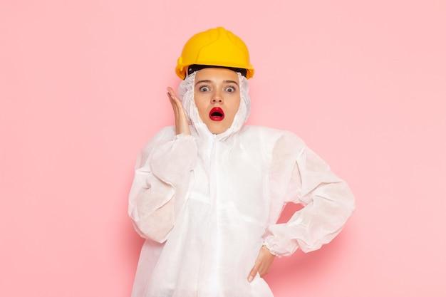 Młoda piękna kobieta w specjalnym białym garniturze i żółtym hełmie z zaskoczonym wyrazem twarzy na różowo