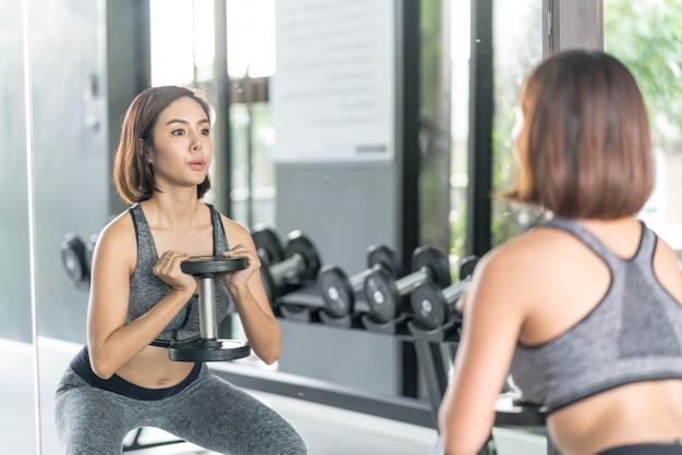 Młoda piękna kobieta w sportowej pracy w siłowni