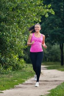 Młoda piękna kobieta w sportowym mundurze biega w lato parku